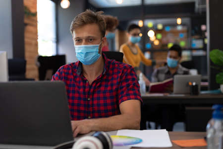 Caucasian man wearing face mask using laptop at desk in casual office. colleagues wearing masks in background. hygiene in workplace during coronavirus covid 19 pandemic. Reklamní fotografie