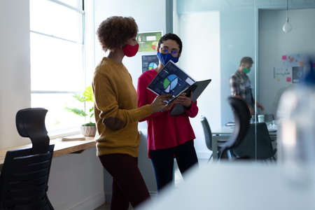 Two mixed race women wearing masks talking in an office. colleagues in discussion looking at documents. hygiene in workplace during coronavirus covid 19 pandemic.