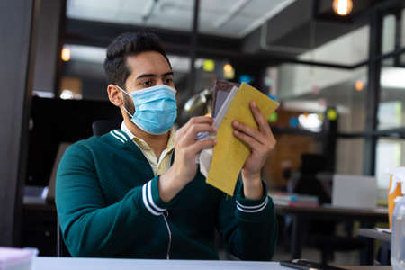 Mixed race man wearing face mask looking at fabric samples in office. hygiene in workplace during coronavirus covid 19 pandemic.