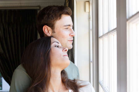 Caucasian couple looking out of window smiling woman leaning on man. self isolation at home during covid 19 coronavirus pandemic.