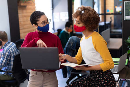 Two mixed race women wearing face masks using laptop and discussing in office. hygiene in workplace during coronavirus covid 19 pandemic.