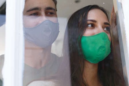 Caucasian couple wearing face masks looking out of window smiling. self isolation at home during covid 19 coronavirus pandemic. Reklamní fotografie