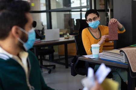 Mixed race woman wearing face mask discussing fabric sample in office. hygiene in workplace during coronavirus covid 19 pandemic.