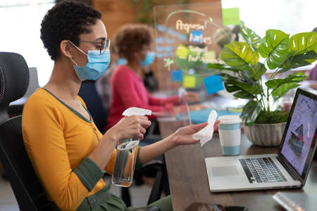 Mixed race woman wearing face mask disinfecting laptop in office. colleague in the background, hygiene screen between them. hygiene in workplace during coronavirus covid 19 pandemic. Reklamní fotografie
