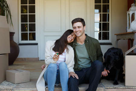 Smiling caucasian couple holding keys sitting outside house with dog. self isolation in new home during covid 19 coronavirus pandemic. Reklamní fotografie