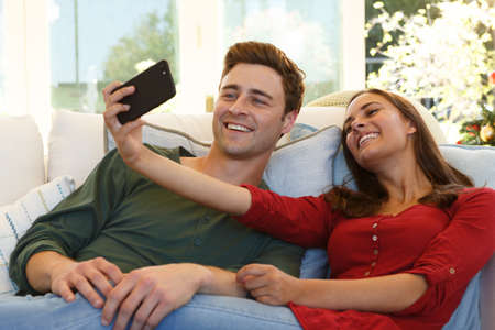 Caucasian couple taking selfie with smartphone sitting on couch smiling. self isolation at home during covid 19 coronavirus pandemic.