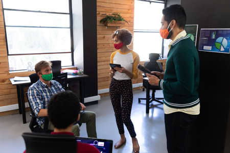 Diverse group of colleagues wearing masks having disussion in creative office. two holding digital tablets. hygiene in workplace during coronavirus covid 19 pandemic.