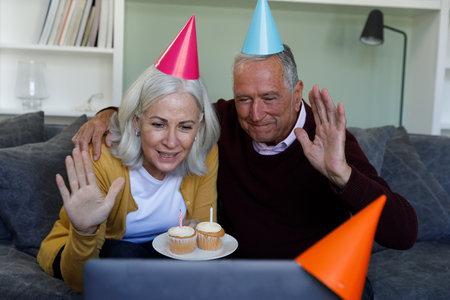 Senior caucasian couple celebrating birthday while having a video chat on laptop at home. social distancing quarantine lockdown during coronavirus pandemic Reklamní fotografie
