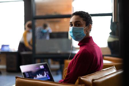 Portrait of mixed race woman wearing face mask working on laptop wearing earphones in casual office. hygiene in workplace during coronavirus covid 19 pandemic. Reklamní fotografie