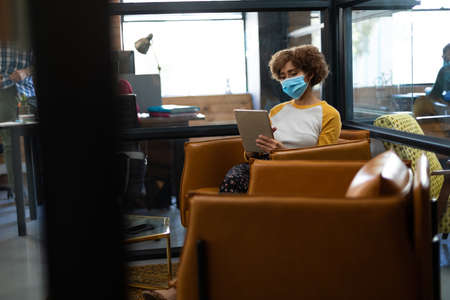 Mixed race woman wearing face mask using tablet in casual office. hygiene in workplace during coronavirus covid 19 pandemic.