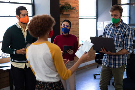 Diverse group of creative colleagues wearing masks having discussion in office. two holding digital tablets. hygiene in workplace during coronavirus covid 19 pandemic.