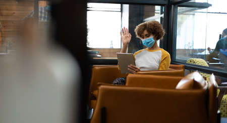 Mixed race woman wearing face mask using tablet and earphones waving during video meeting. hygiene in workplace during coronavirus covid 19 pandemic. Reklamní fotografie