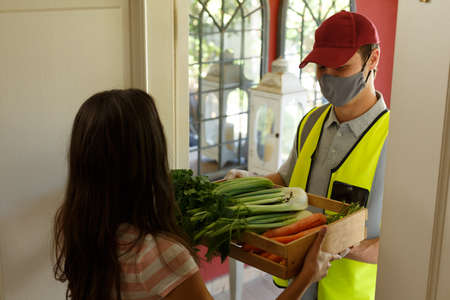 Caucasian woman taking food box from delivery man wearing face mask at front door. self isolation at home during covid 19 coronavirus pandemic. Reklamní fotografie