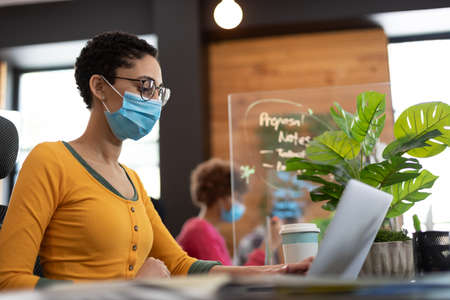 Mixed race woman wearing face mask working at desk in office. male colleague in background hygiene screen between them. hygiene in workplace during coronavirus covid 19 pandemic. Reklamní fotografie