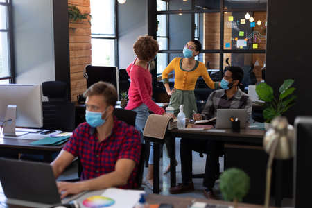 Diverse colleagues wearing face masks discussing at desk in casual office. man in face mask using lasptop at desk in foreground. hygiene in workplace during coronavirus covid 19 pandemic. Reklamní fotografie