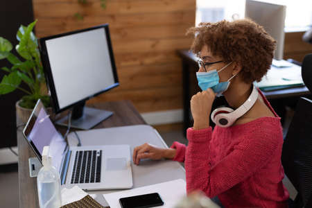 Mixed race woman wearing face mask using laptop at desk in casual office. sanitizing gel on her desk. hygiene in workplace during coronavirus covid 19 pandemic.