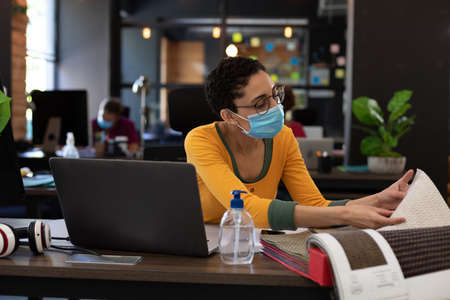 Mixed race woman wearing face mask looking at fabric samples in office. hygiene in workplace during coronavirus covid 19 pandemic. Reklamní fotografie