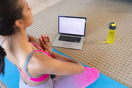 Mixed race woman practising yoga at home using her laptop. self isolation during covid 19 coronavirus pandemic.