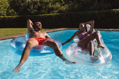 Two diverse male and female friends having fun playing on inflatables in swimming pool. Hanging out and relaxing outdoors in summer.