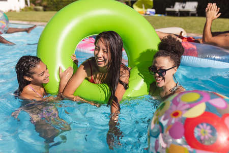Diverse group of friends having fun playing on inflatables in swimming pool. Hanging out and relaxing outdoors in summer.