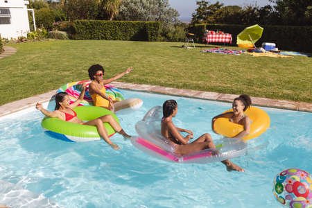 Diverse group of female friends having fun playing on inflatables in swimming pool. Hanging out and relaxing outdoors in summer.