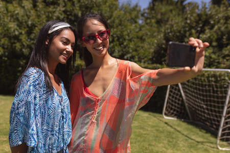 Two mixed race female friends taking selfie at a pool party. Hanging out and relaxing outdoors in summer.