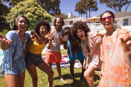Diverse group of friends having fun and smiling at a pool party. Hanging out and relaxing outdoors in summer.