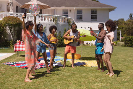 Diverse group of friends dancing and smiling at a pool party. Hanging out and relaxing outdoors in summer. Standard-Bild