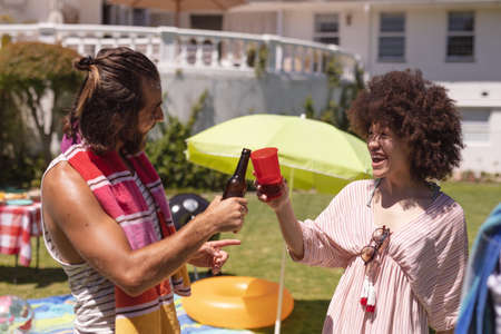 Two diverse male and female friends drinking and making a toast at a pool party. hanging out, celebrating and relaxing outdoors in summer.