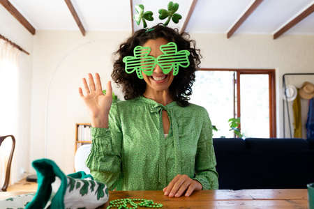 Caucasian woman dressed in green with shamrock glasses for st patrick's day waving during video call. staying at home in self isolation during quarantine lockdown. Standard-Bild