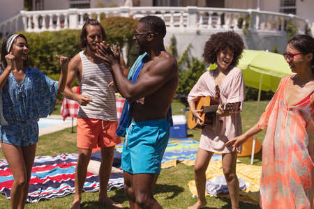 Diverse group of friends having fun at a pool party. hanging out, playing guitar, dancing and relaxing outdoors in summer.