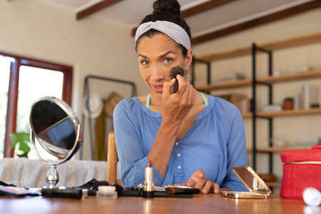 Portrait of caucasian woman applying makeup, holding makeup brush at home. Staying at home in self isolation during quarantine lockdown.