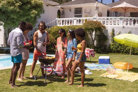 Diverse group of friends having barbecue and talking at a pool party. hanging out,drinking beer and relaxing outdoors in summer.