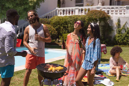 Diverse group of friends having barbecue and talking at a pool party. hanging out, drinking beer and relaxing outdoors in summer. Standard-Bild