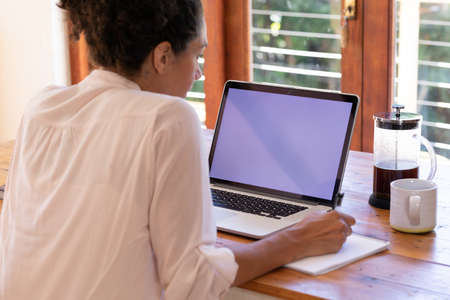 Caucasian woman using laptop working from home, making notes. Staying at home in self isolation during quarantine lockdown.