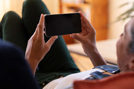 Caucasian woman using smartphone lying on sofa at home. Staying at home in self isolation during quarantine lockdown.