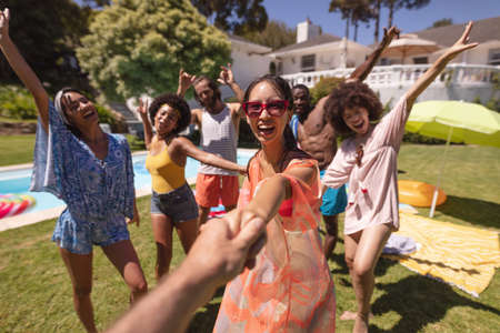 Diverse group of happy friends having fun dancing at a pool party. hanging out, and posing for the camera outdoors in summer. Standard-Bild