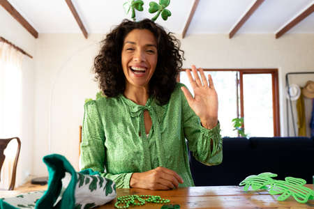 Caucasian woman dressed in green with shamrock deely boppers for st patrick's day waving during video call. staying at home in self isolation during quarantine lockdown.