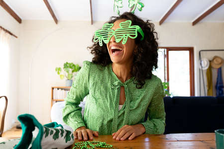 Caucasian woman dressed in green with shamrock glasses for st patrick's day laughing. Staying at home in self isolation during quarantine lockdown.