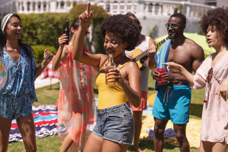 Diverse group of friends having fun and dancing at a pool party. Hanging out with drinks and dancing on the garden lawn in summer. Standard-Bild