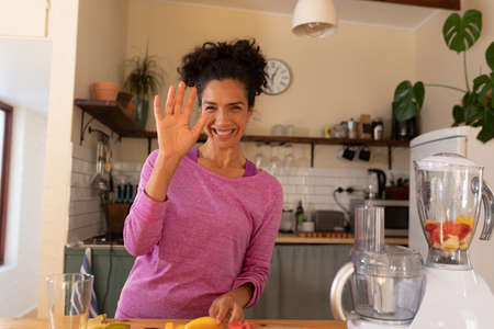 Happy caucasian woman vlogging and waving in kitchen at home. Staying at home in self isolation during quarantine lockdown.