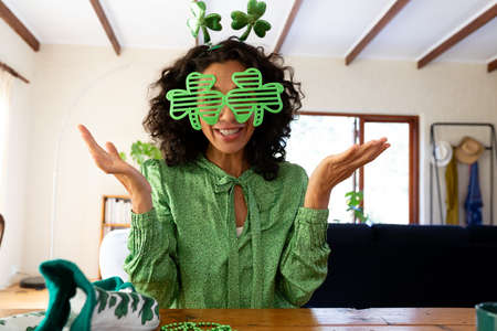 Caucasian woman dressed in green with shamrock glasses making st patrick's day video call. staying at home in self isolation during quarantine lockdown.