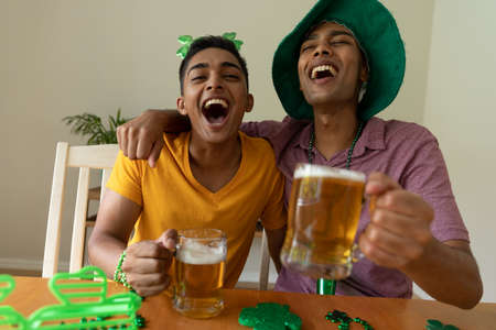 Laughing mixed race gay male couple wearing st patrick's day costumes and holding glasses of beer. staying at home in isolation during quarantine lockdown. Standard-Bild