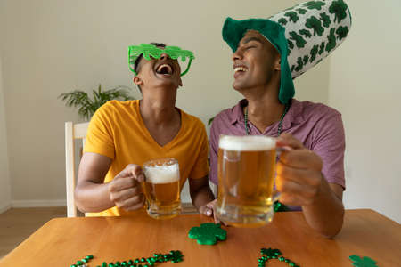 Laughing mixed race gay male couple wearing st patrick's day costumes and raising glasses of beer. staying at home in isolation during quarantine lockdown. Standard-Bild