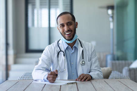Portrait of mixed race male doctor wearing face mask looking at the camera and smiling. Hygiene healthcare protection during coronavirus covid 19 pandemic