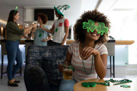 Portrait of mixed race woman wearing shamrock glasses celebrating st patrick's at a bar. fun with friends during celebration of the irish patron saint's day.