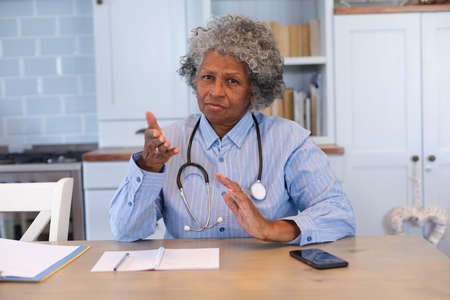 Portrait of african american senior female doctor talking looking at the camera at home. distant communication and telemedicine consultation concept. Standard-Bild
