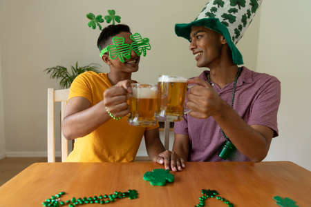 Happy mixed race gay male couple wearing st patrick's day costumes toasting with beer glasses. staying at home in isolation during quarantine lockdown.
