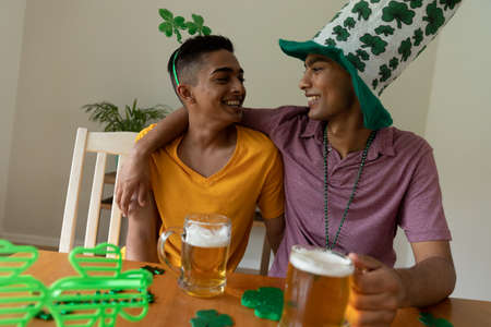 Smiling mixed race gay male couple wearing st patrick's day costumes embracing and holding beers. staying at home in isolation during quarantine lockdown. Standard-Bild