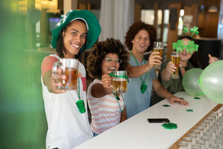 Diverse group of happy friends celebrating st patrick's day raising glasses of beer at a bar. fun during celebration of the irish patron saint's day. Standard-Bild